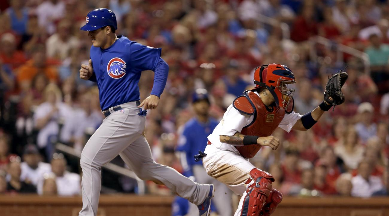 Chicago Cubs' Anthony Rizzo, left, scores on a sacrifice fly by Jorge Soler as St. Louis Cardinals catcher Yadier Molina waits for the throw during the third inning of a baseball game Tuesday, May 5, 2015, in St. Louis. (AP Photo/Jeff Roberson)