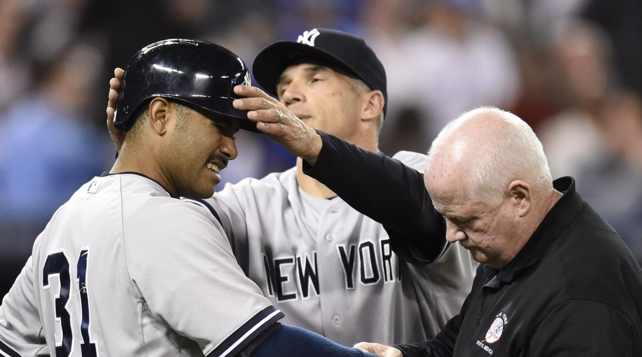 New York Yankees' Gregorio Petit's arm is tended to by a trainer as Yankees manager Joe Girardi removes Petit's batting helmet after being hit by a pitch from Toronto Blue Jays' Chad Jenkins during the eighth inning of a baseball game Tuesday, May 5, 2015