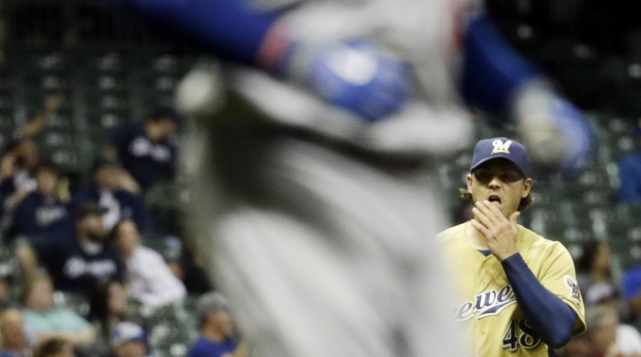 Milwaukee Brewers relief pitcher Neal Cotts watches as Los Angeles Dodgers' Adrian Gonzalez rounds the bases after hitting a two-run home run during the seventh inning of a baseball game Tuesday, May 5, 2015, in Milwaukee. (AP Photo/Morry Gash)