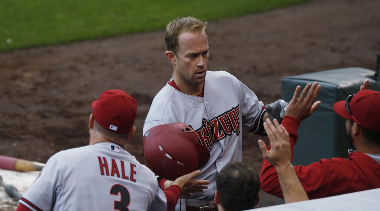 Arizona Diamondbacks manager Chip Hale, left, congratulates Arizona Diamondbacks third baseman Aaron Hill as he returns to the dugout after hitting a three-run home run against the Colorado Rockies in the fourth inning of the first game of a baseball doub