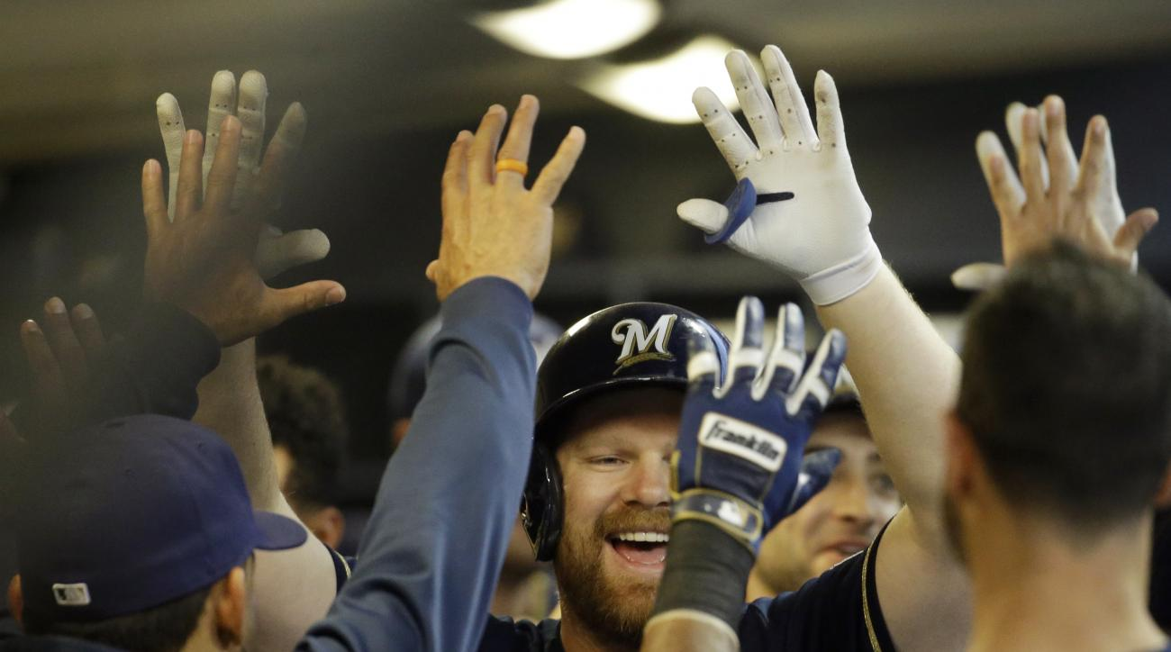 Milwaukee Brewers' Adam Lind is congratulated in the dugout after hitting a two-run home run during the first inning of a baseball game against the Los Angeles Dodgers Wednesday, May 6, 2015, in Milwaukee. (AP Photo/Morry Gash)