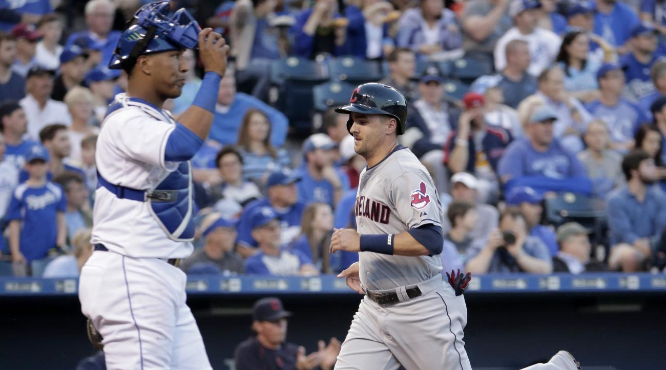 Cleveland Indians' Lonnie Chisenhall (8) runs home past Kansas City Royals catcher Salvador Perez to score on a single by Jason Kipnis during the second inning of a baseball game Wednesday, May 6, 2015, in Kansas City, Mo. (AP Photo/Charlie Riedel)