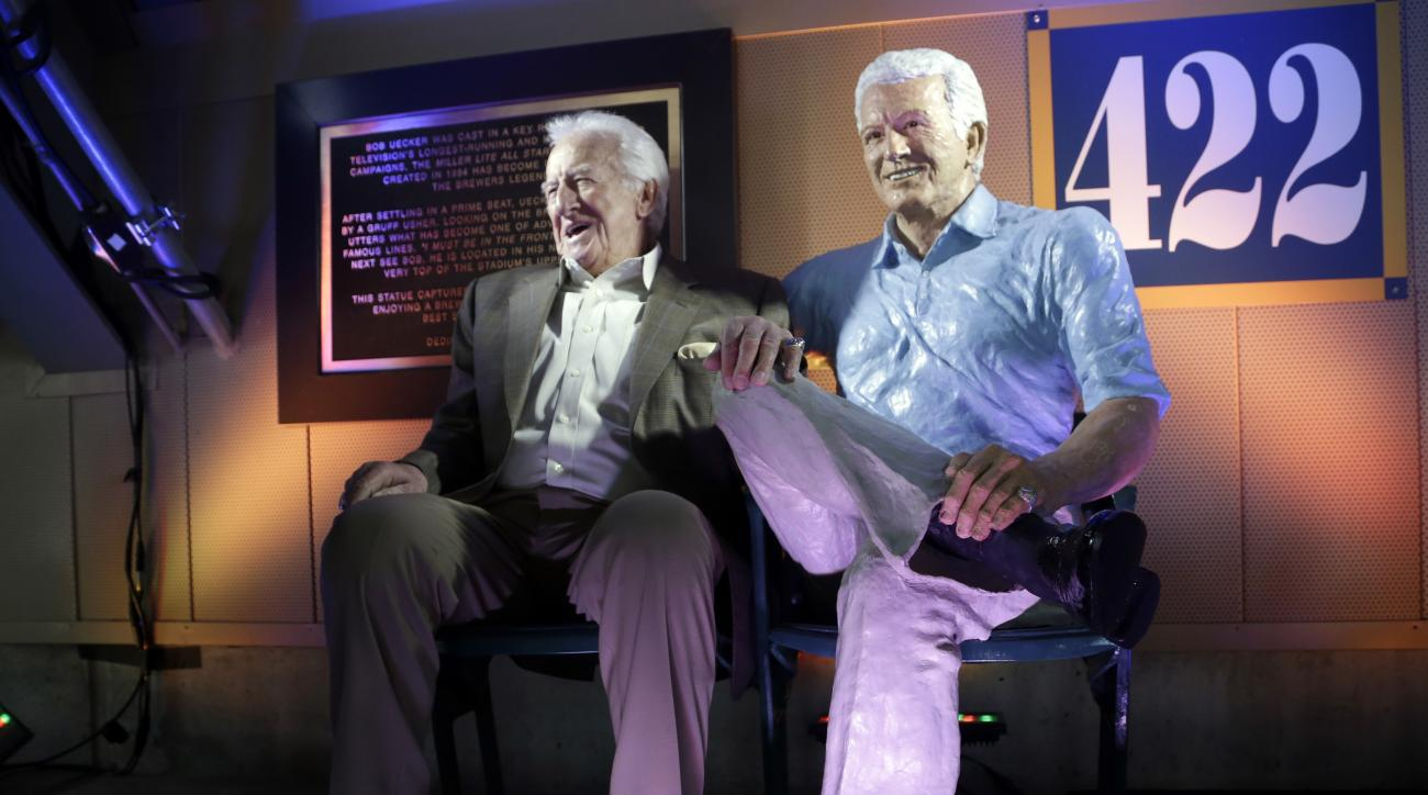 FILE - In this April, 2014 file photo, Milwaukee Brewers radio announcer Bob Uecker sits next to his statue at Miller Park in Milwaukee. Uecker was locked in the radio booth at Miller Park when the door handle broke during the sixth inning against the Dod