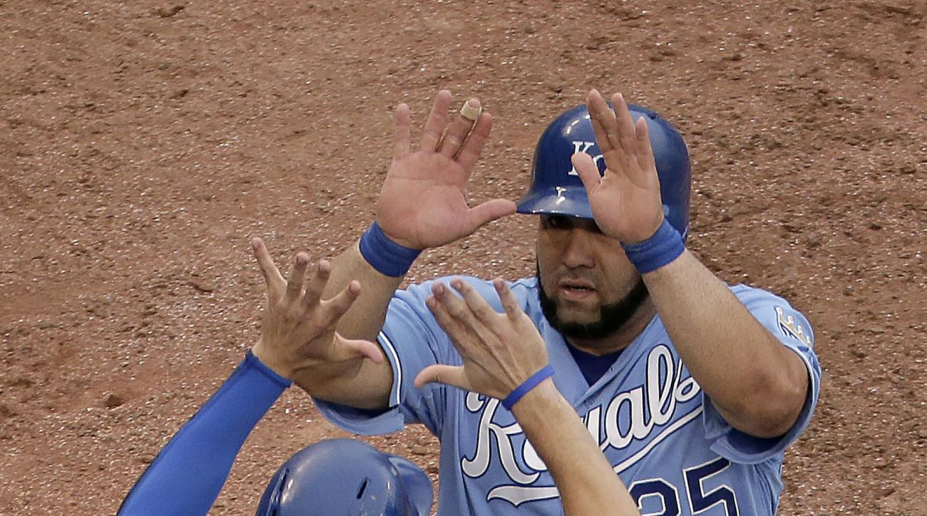 Kansas City Royals' Kendrys Morales (25) and Eric Hosmer (35) celebrate after scoring on a two-run double hit by Omar Infante during the seventh inning of a baseball game against the Cleveland Indians Thursday, May 7, 2015, in Kansas City, Mo. (AP Photo/C