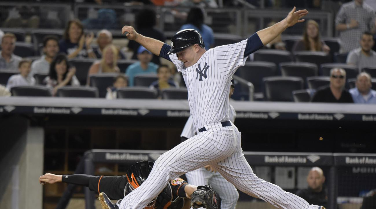 New York Yankees' Brian McCann, foreground, is tagged out by Baltimore Orioles catcher Caleb Joseph while attempting to score on a two-RBI double by Carlos Beltran during the third inning of a baseball game Friday, May 8, 2015, at Yankee Stadium in New Yo
