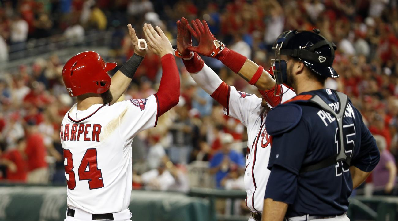 Washington Nationals' Bryce Harper (34) celebrates his two-run homer with Yunel Escobar, right, in front of Atlanta Braves catcher A.J. Pierzynski (15) during the sixth inning of a baseball game at Nationals Park, Friday, May 8, 2015, in Washington. (AP P
