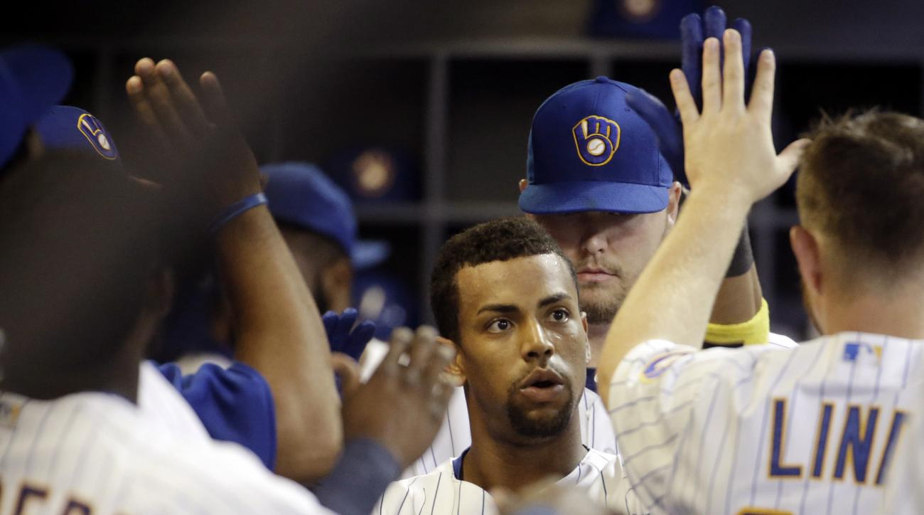 Milwaukee Brewers' Khris Davis is congratulated in the dugout after hitting a home run during the sixth inning of a baseball game against the Chicago Cubs, Friday, May 8, 2015, in Milwaukee. (AP Photo/Morry Gash)