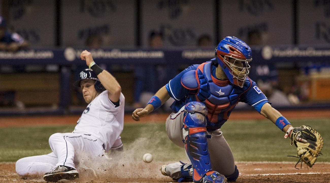 Tampa Bay Rays' Evan Longoria, left, scores on Jake Elmore's RBI-single as Texas Rangers catcher Carlos Corporan tries to block the throw to the plate during the eighth inning of a baseball game Friday, May 8, 2015, in St. Petersburg, Fla. The ball hit th