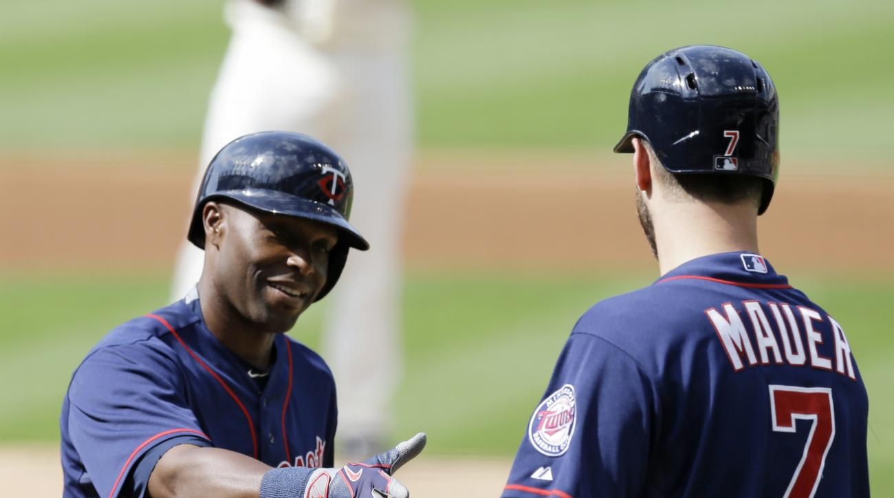 Minnesota Twins' Torii Hunter, left, is congratulated by Joe Mauer after Hunter hit a solo home run off Cleveland Indians starting pitcher Bruce Chen in the first inning of a baseball game, Saturday, May 9, 2015, in Cleveland. (AP Photo/Tony Dejak)