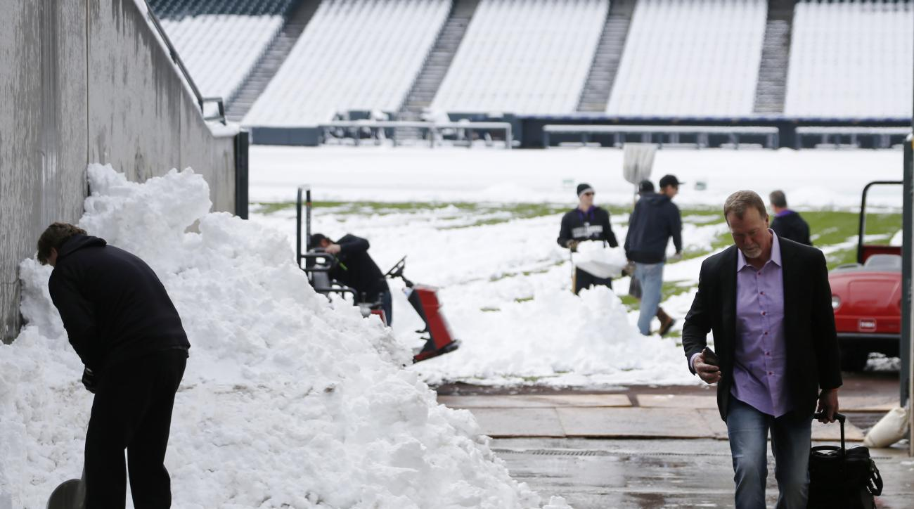 Los Angeles Dodgers hitting coach Mark McGwire, right, heads to the visiting team's clubhouse after taking a photograph of grounds crew members clearing snow from the outfield of Coors Field following a storm that left a wet, heavy snowfall Sunday, May 10