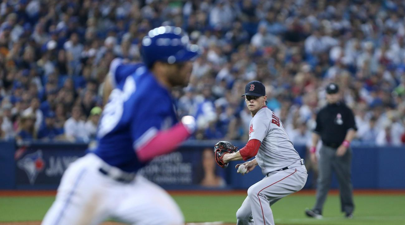 Boston Red Sox starting pitcher Clay Buchholz (11) gets set to throw out Toronto Blue Jays second baseman Devon Travis (29) during the third inning AL baseball in Toronto on Sunday, May 10, 2015. (Peter Power(/The Canadian Press via AP) MANDATORY CREDIT
