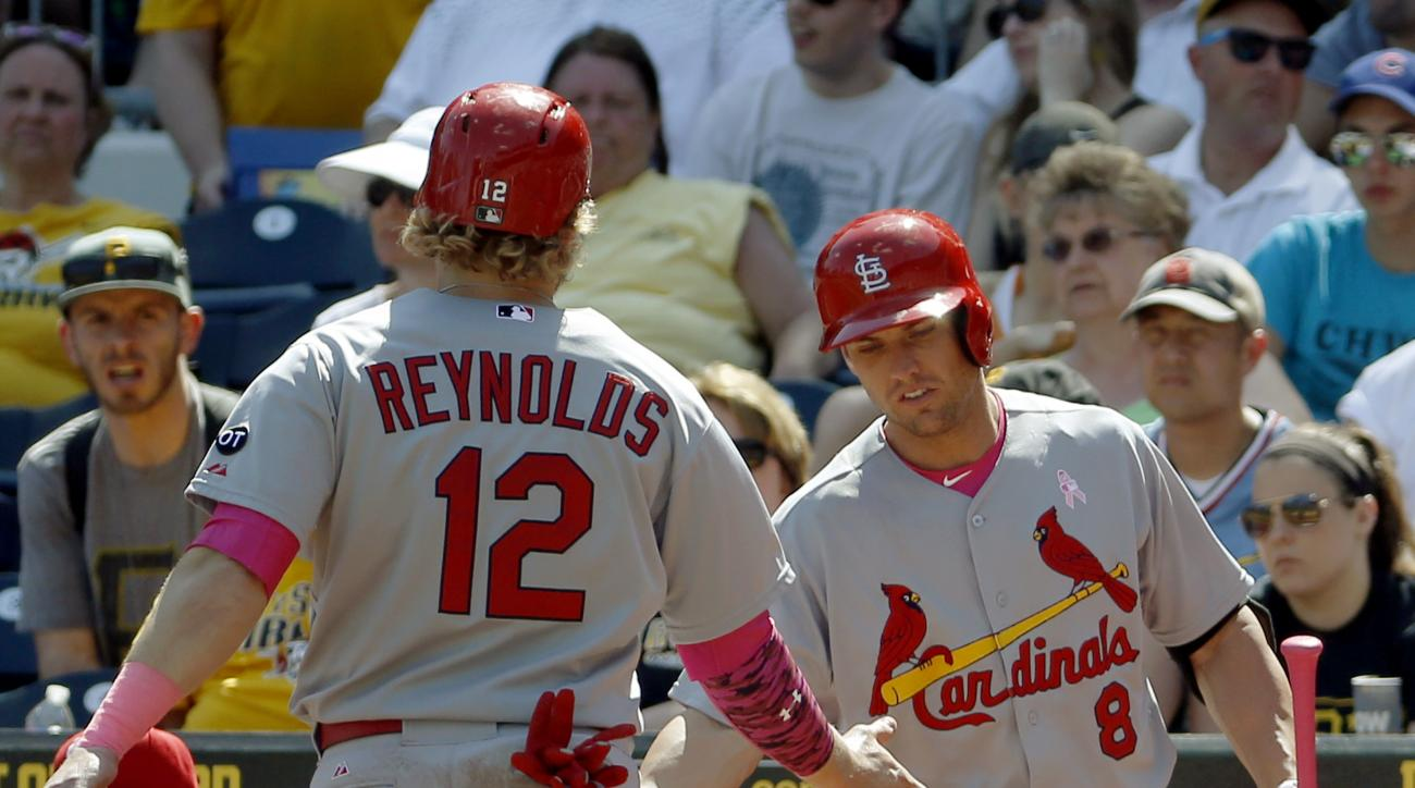 St. Louis Cardinals' Mark Reynolds (12) is greeted by Peter Bourjos (8) after scoring from third on a hit by Jason Heyward in the seventh inning of a baseball game, Sunday, May 10, 2015, in Pittsburgh. The Pirates won 4-3. (AP Photo/Keith Srakocic)