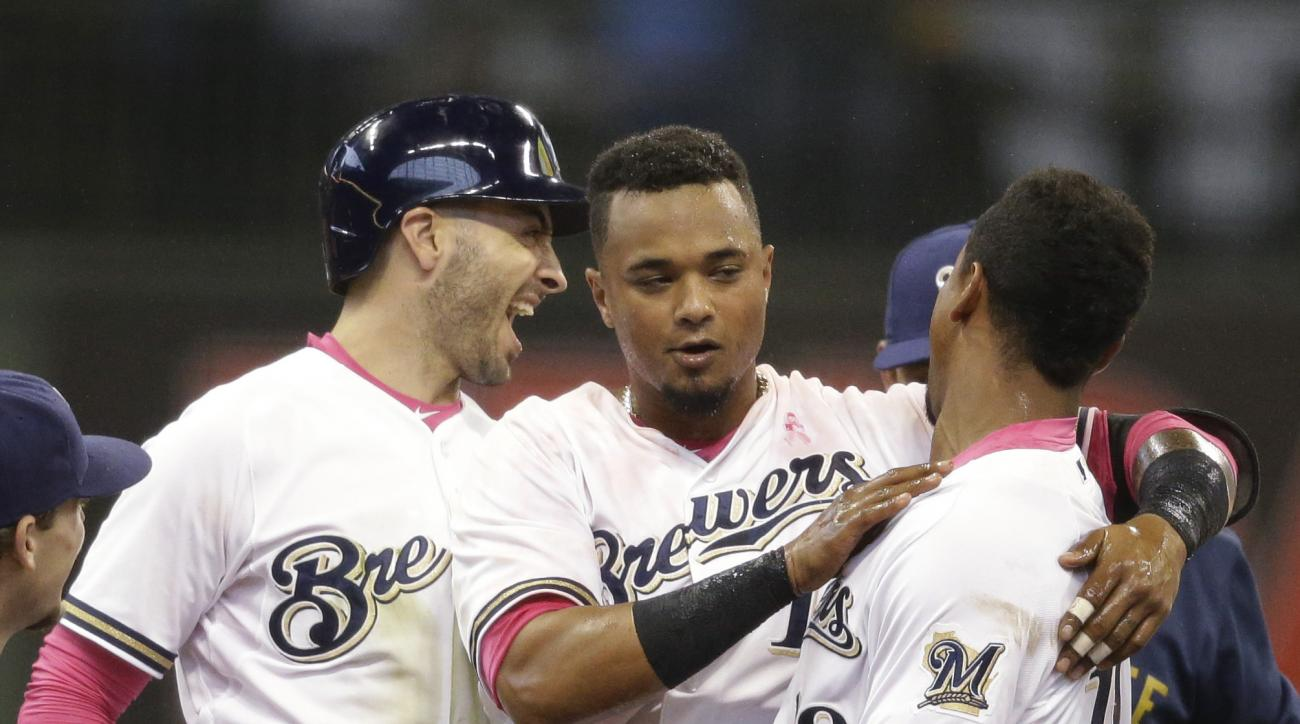 Milwaukee Brewers catcher Martin Maldonado, center, celebrates with Khris Davis, right, and Ryan Braun after he hit the game-winning single against the Chicago Cubs during the eleventh inning of a baseball game Sunday, May 10, 2015, in Milwaukee. The Brew
