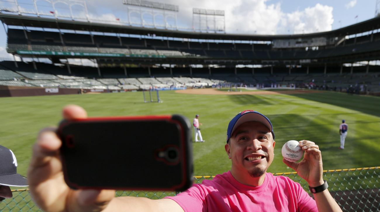 Carlos Ayala, from Chicago, takes a selfie with a ball tossed to him in the left field bleachers by Cubs pitcher Jason Hammel, during batting practice before a baseball game against the New York Mets Monday, May 11, 2015, in Chicago. The Cubs opened the f