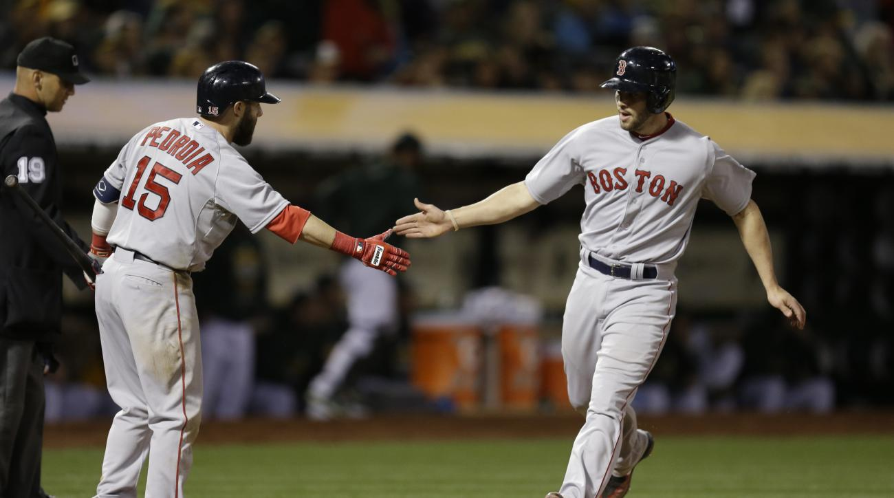 Boston Red Sox' Blake Swihart, right, is congratulated by Dustin Pedroia (15) after Swihart scored against the Oakland Athletics in the fifth inning of a baseball game Monday, May 11, 2015, in Oakland, Calif. (AP Photo/Ben Margot)