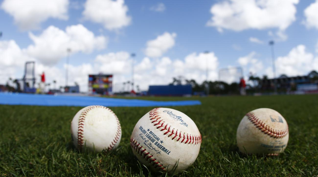 FILE- In this March 12, 2015, file photo, baseballs sit shown on the field before an exhibition spring training baseball game between New York Mets and Washington Nationals in Port St. Lucie, Fla. Major League Baseball changed how balls are handled before