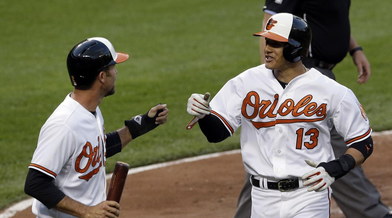 Baltimore Orioles' J.J. Hardy, left, and Manny Machado bump fists after scoring on a single by Jimmy Paredes during the third inning of a baseball game against the Toronto Blue Jays, Tuesday, May 12, 2015, in Baltimore. (AP Photo/Patrick Semansky)