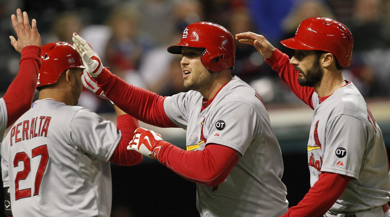 St. Louis Cardinals Matt Holiday, center, is congratulated by teammates Jhonny Peralta (27) and Matt Carpenter after hitting a solo home run during the eighth inning of a baseball game against the Cleveland Indians on Tuesday, May 12, 2015, in Cleveland.