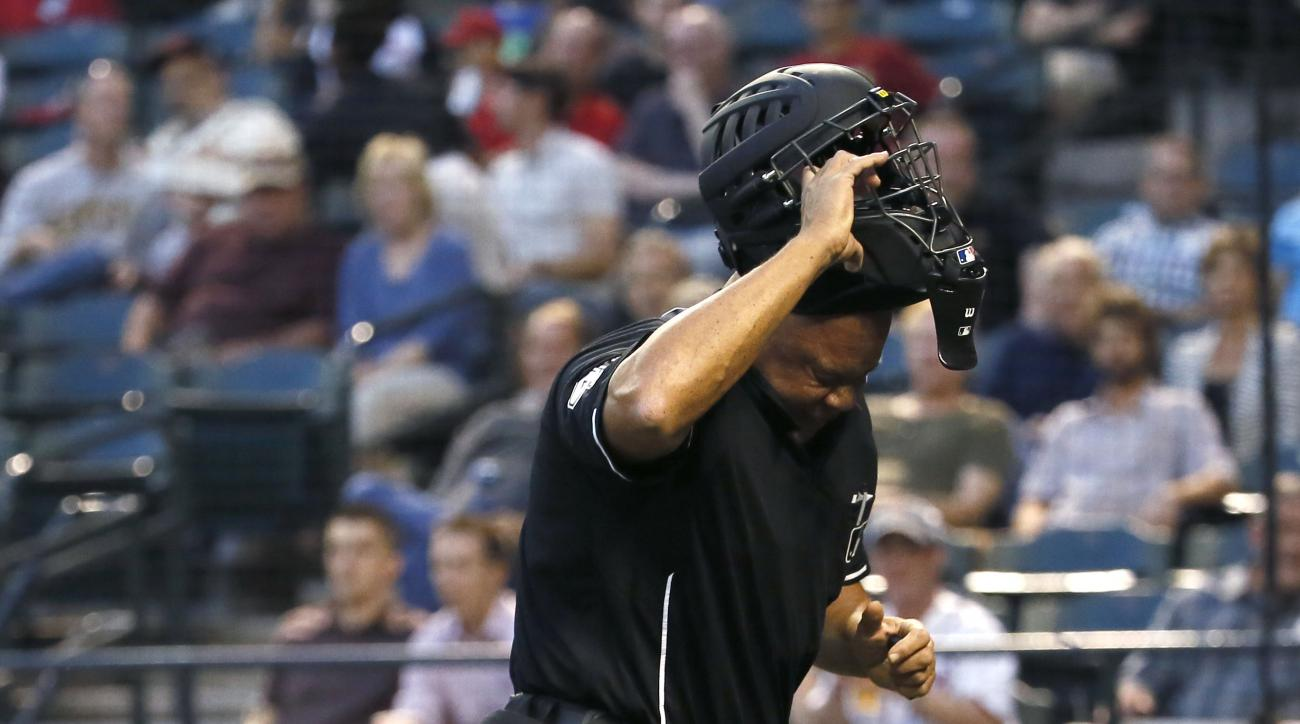 Home plate umpire Kerwin Danley throws off his mask after being hit in the face by a foul ball by Arizona Diamondbacks' Nick Ahmed during the second inning of a baseball game against the Washington Nationals, Tuesday, May 12, 2015, in Phoenix. (AP Photo/M