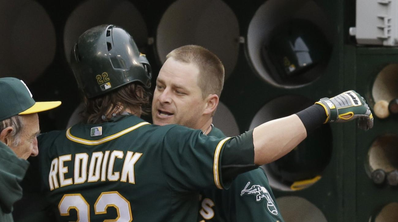 Oakland Athletics' Stephen Vogt, right, celebrates with Josh Reddick (22) after Vogt hit a two-run home run off Boston Red Sox pitcher Justin Masterson during the first inning of a baseball game Tuesday, May 12, 2015, in Oakland, Calif. (AP Photo/Ben Marg