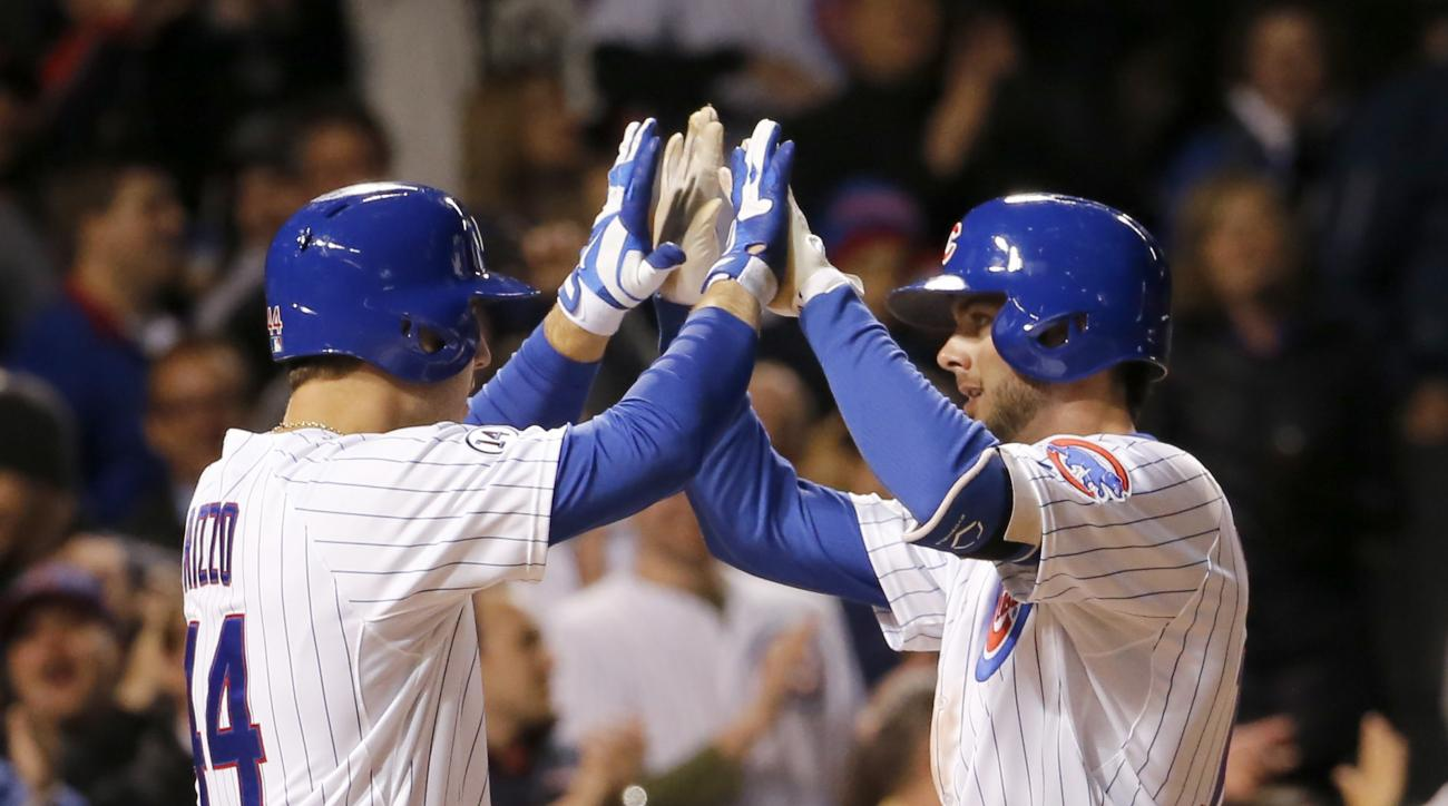 Chicago Cubs' Anthony Rizzo, left, greets Kris Bryant at home after Bryant's home run off New York Mets relief pitcher Hansel Robles during the eighth inning of a baseball game Tuesday, May 12, 2015, in Chicago. (AP Photo/Charles Rex Arbogast)
