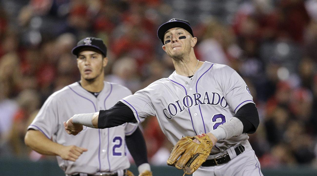 Colorado Rockies shortstop Troy Tulowitzki throws the ball to first base for the out on Los Angeles Angels' Johnny Giavotella as third baseman Nolan Arenado watches during the sixth inning of a baseball game, Tuesday, May 12, 2015, in Anaheim, Calif. (AP