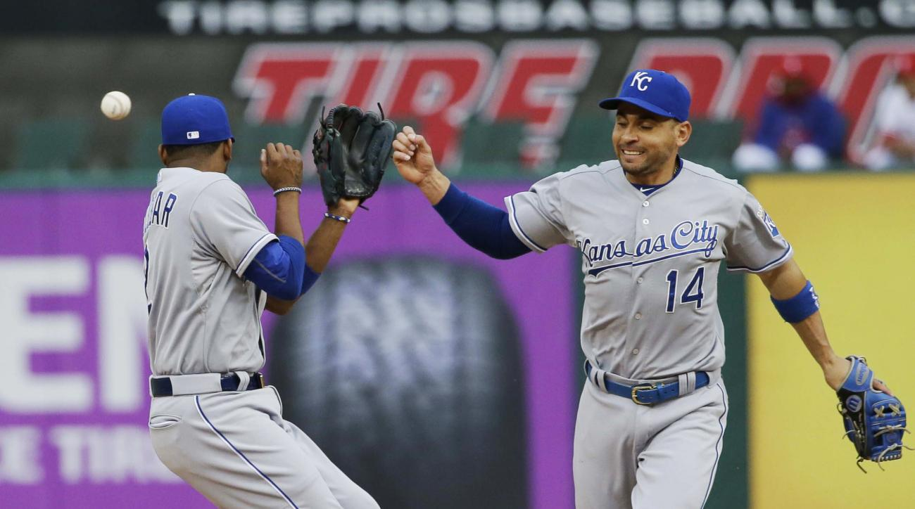 Kansas City Royals second baseman Omar Infante (14) and shortstop Alcides Escobar (2) misplay a hopper allowing a single by Texas Rangers Delino DeShields during the second inning of a baseball game in Arlington, Texas, Wednesday, May 13, 2015. (AP Photo/