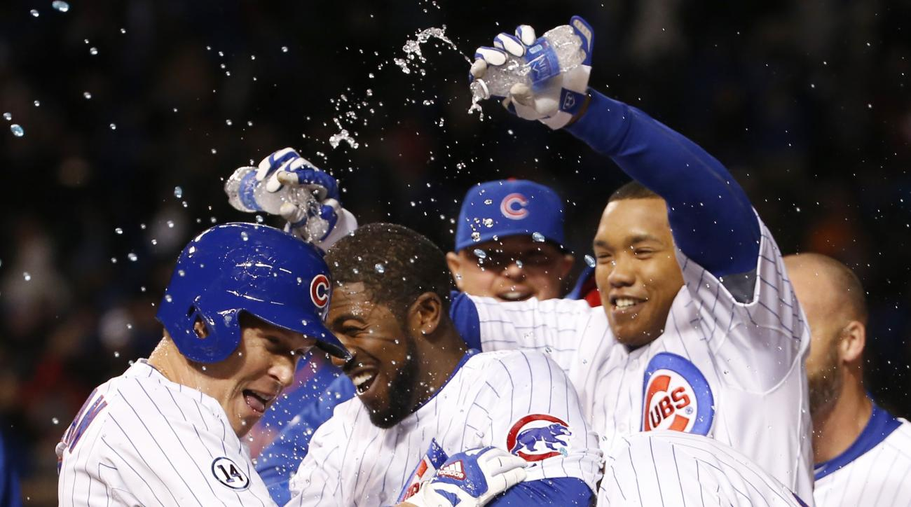 Chicago Cubs' Chris Coghlan, left, celebrates with teammates after he drew a bases loaded walk from New York Mets relief pitcher Jeurys Familia, in the bottom of the ninth, scoring Matt Szczur after a baseball game Wednesday, May 13, 2015, in Chicago. The