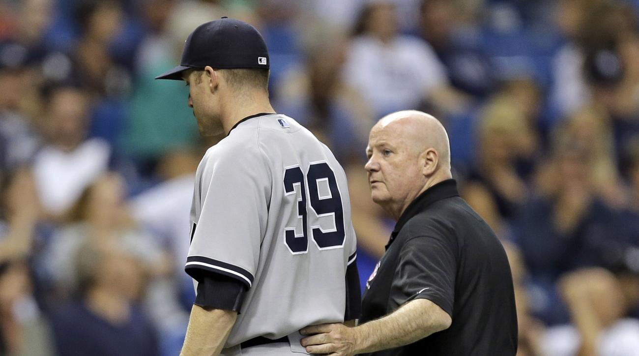 New York Yankees trainer Steve Donohue, right, assists starting pitcher Chase Whitley off the field after Whitley injured himself during the second inning of the Yankees' baseball game against the Tampa Bay Rays on Thursday, May 14, 2015, in St. Petersbur