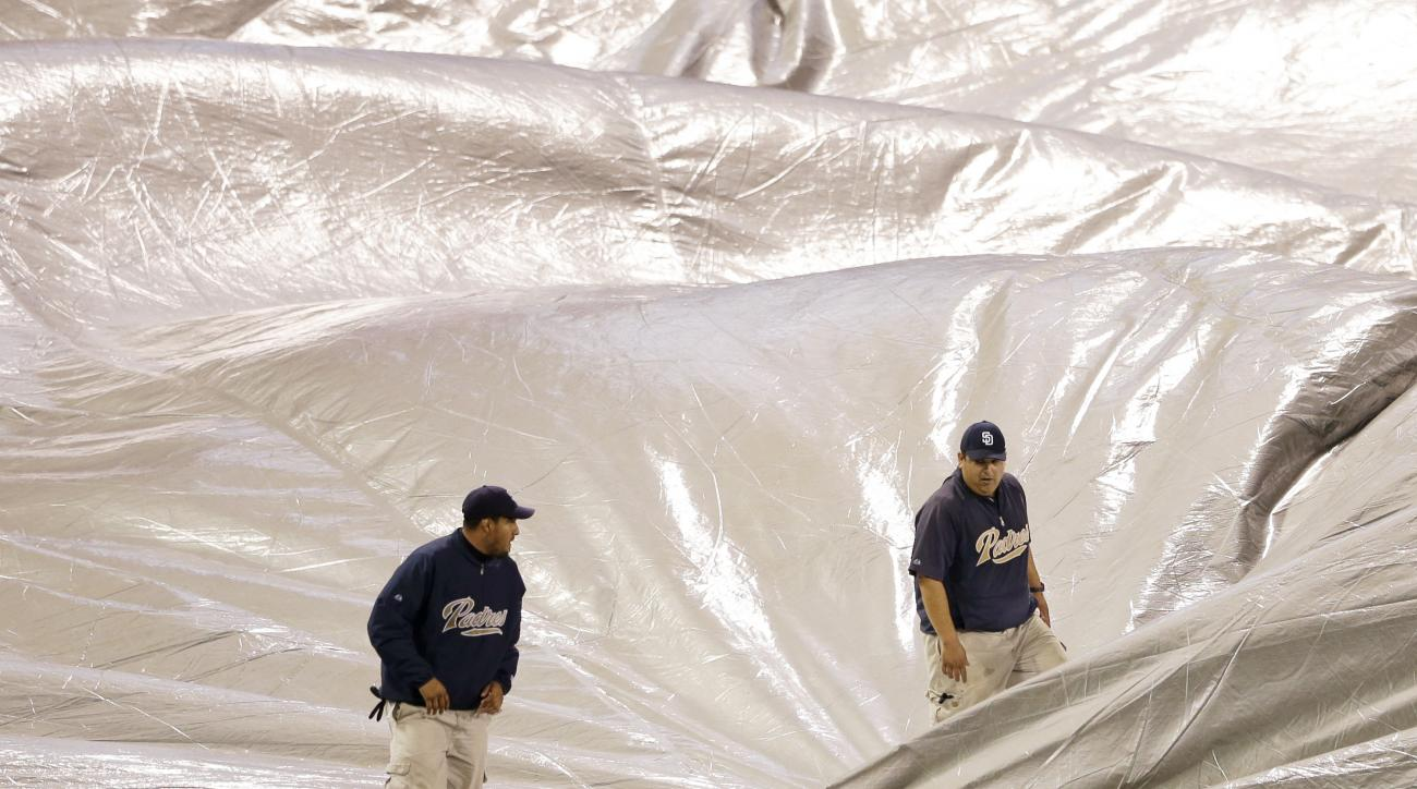 San Diego Padres grounds crew members remove a tarp during a rain delay in the Padres' baseball game against the Washington Nationals on Thursday, May 14, 2015, in San Diego. (AP Photo/Gregory Bull)