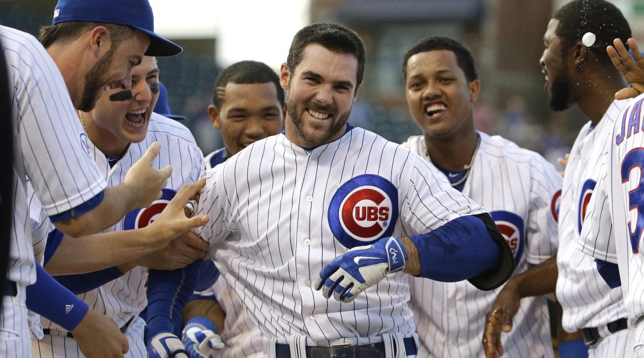 Chicago Cubs' Matt Szczur, center, celebrates with teammates after hitting the game-winning single during the 12th inning of a baseball game against the Pittsburgh Pirates in Chicago, Friday, May 15, 2015. The Cubs won 11-10. (AP Photo/Nam Y. Huh)