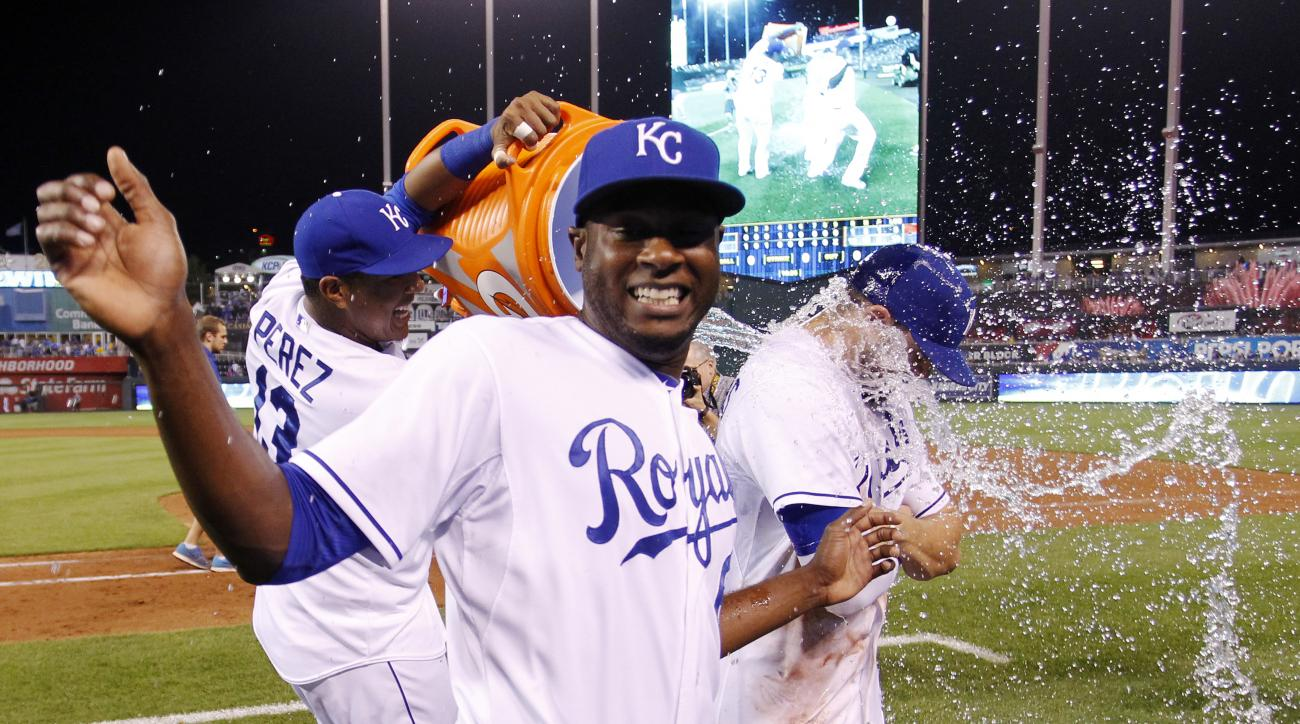Kansas City Royals' Lorenzo Cain, foreground, moves to avoid getting wet as Salvador Perez, left, douses Mike Moustakas, right, at the conclusion of baseball game against the New York Yankees at Kauffman Stadium in Kansas City, Mo., Friday, May 15, 2015.