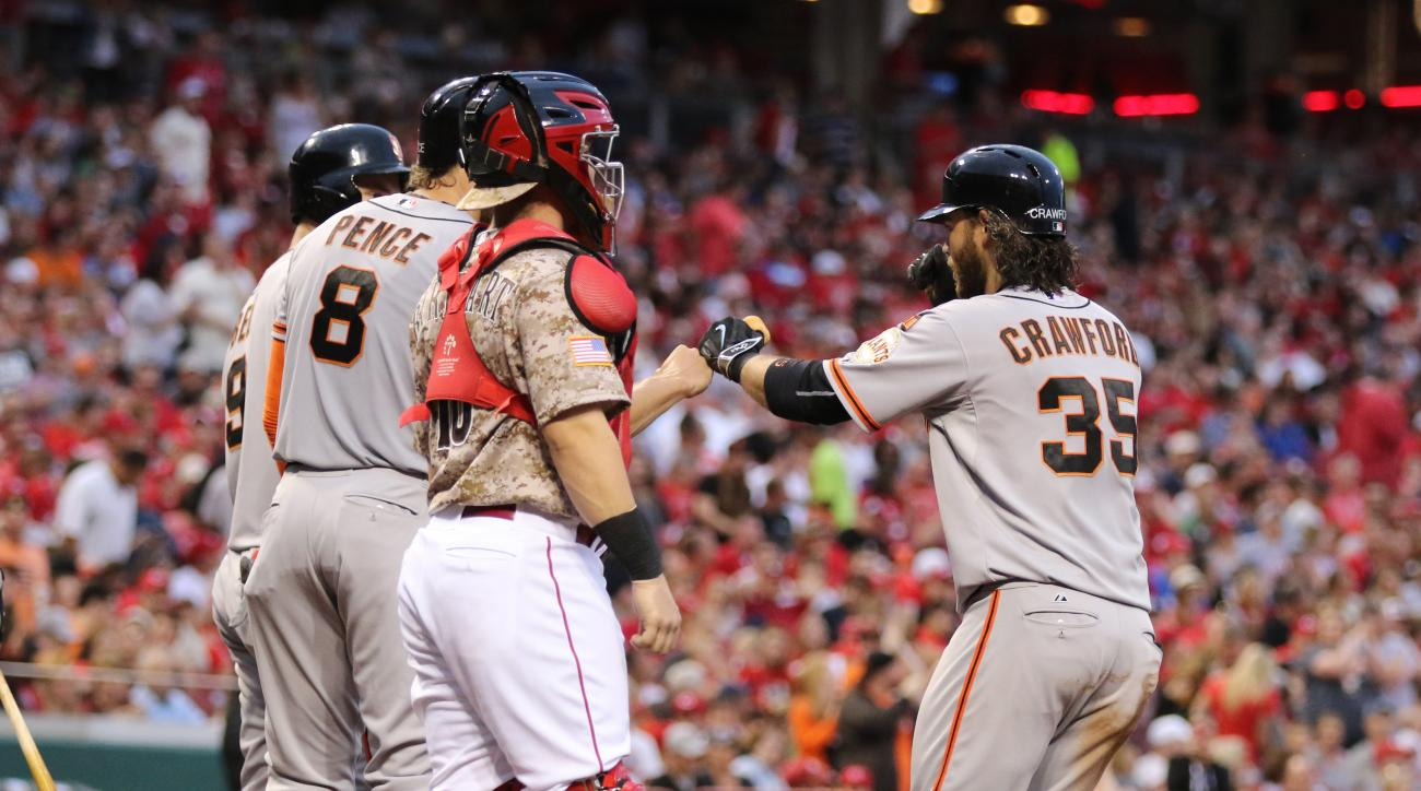 San Francisco Giants' Brandon Crawford (35) fists-bumps teammates after a grand slam off Cincinnati Reds starting pitcher Mike Leake during the fifth inning of a baseball game Saturday, May 16, 2015, in Cincinnati. (AP Photo/Gary Landers)