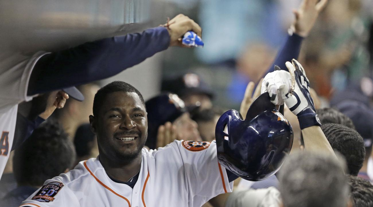 Houston Astros' Chris Carter (23) is congratulated in the dugout after hitting a three-run home run against the Toronto Blue Jays in the sixth inning of a baseball game Saturday, May 16, 2015, in Houston. (AP Photo/Pat Sullivan)