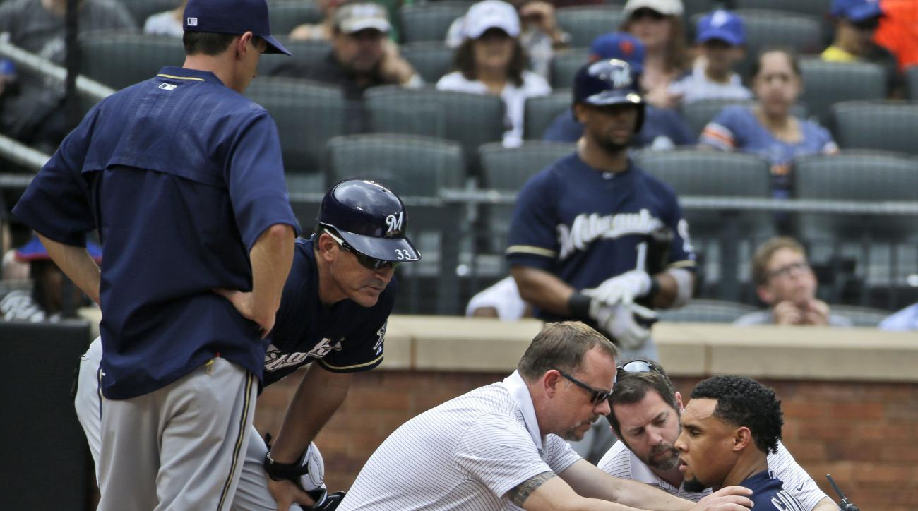 Trainers examine Milwaukee Brewers' Carlos Gomez, right, after he was hit by a pitch during the sixth inning of the baseball game against the New York Mets at Citi Field, Sunday, May 17, 2015 in New York. (AP Photo/Seth Wenig)