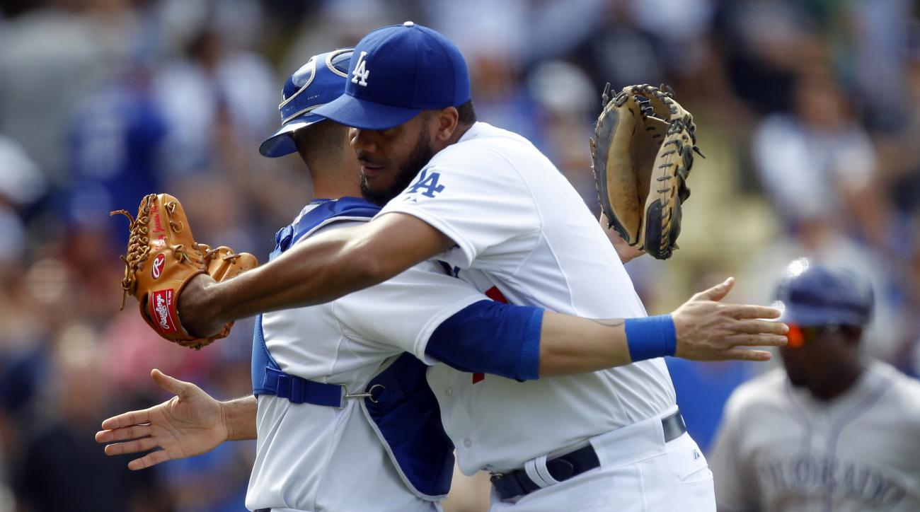 Los Angeles Dodgers relief pitcher Kenley Jansen, right, gets a hug from catcher Yasmani Grandal after closing out the ninth inning to defeat the Colorado Rockies 1-0 in a baseball game in Los Angeles, Sunday, May 17, 2015. (AP Photo/Alex Gallardo)