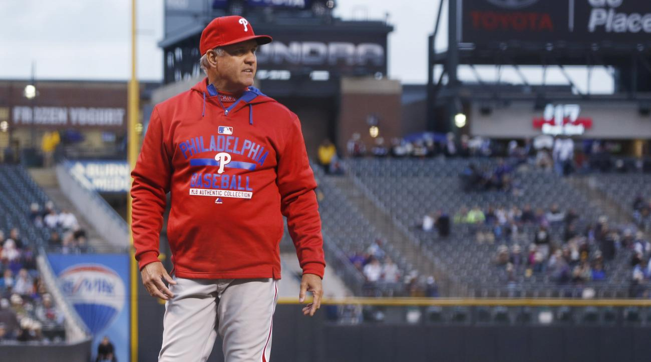 Philadelphia Phillies manager Ryne Sandberg argues with umpires as they review to see if Philadelphia Phillies shortstop Freddy Galvis was safe at first base after Colorado Rockies first baseman Wilin Rosario failed to touch the bases while fielding a gro
