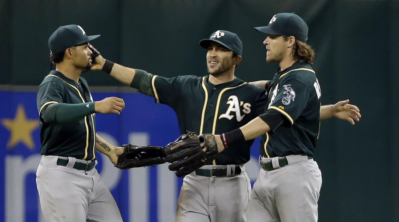 Oakland Athletics outfielders Coco Crisp, left, Sam Fuld, center and Josh Reddick celebrate after beating the Houston Astros in a baseball game 2-1 Monday, May 18, 2018, in Houston. (AP Photo/David J. Phillip)