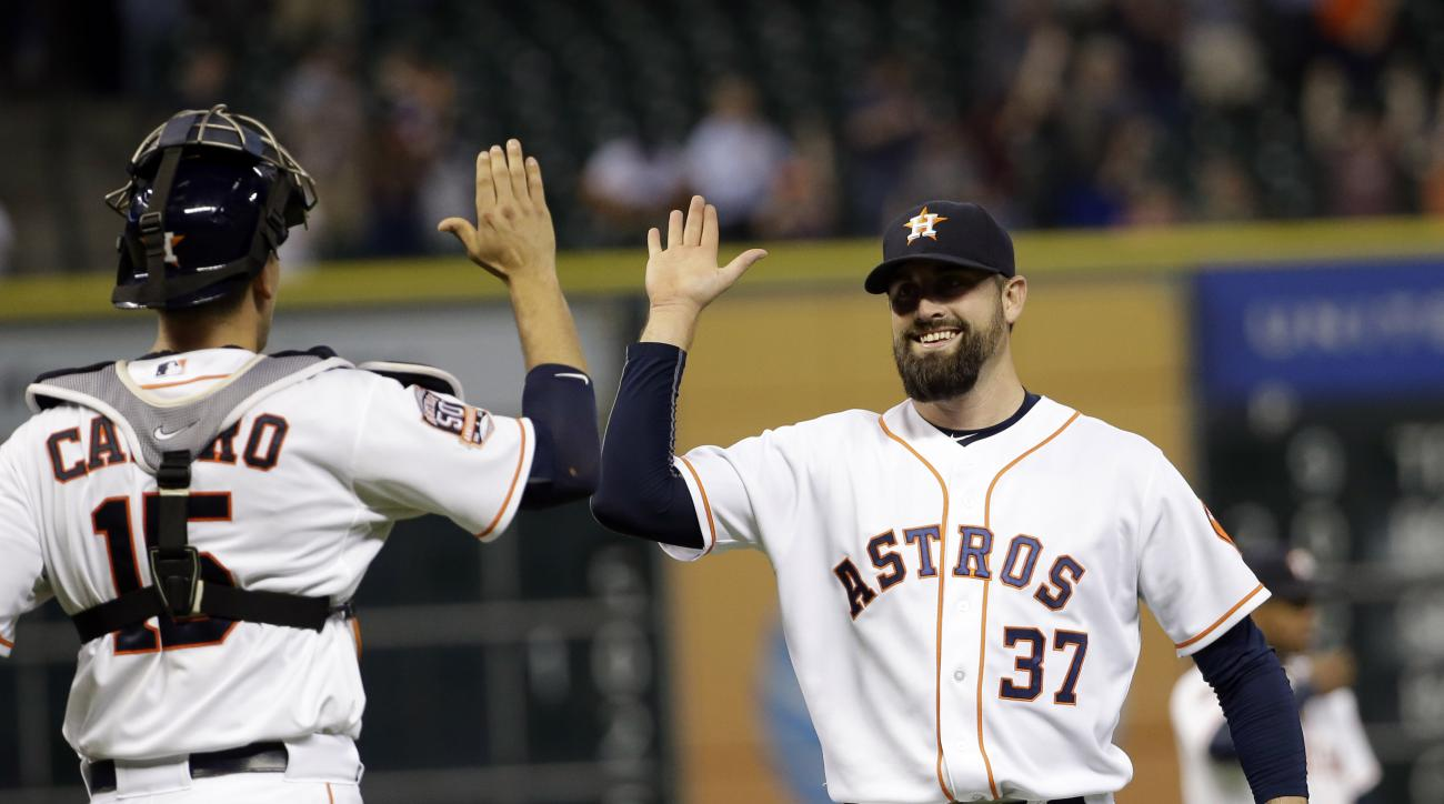 Houston Astros relief pitcher Pat Neshek (37) celebrates with catcher Jason Castro (15) after the Astros defeated the Oakland Athletics 6-4 in a baseball game Tuesday, May 19, 2015, in Houston. (AP Photo/David J. Phillip)