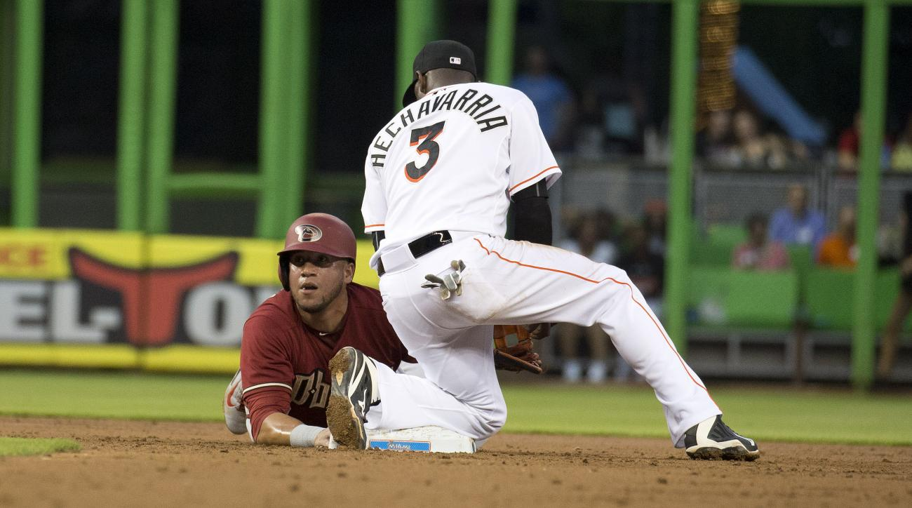 Arizona Diamondbacks  David Peralta (6) jumps back safe to second base on a throw to Miami Marlins shortstop Adeiny Hechavarria (3) during the third inning of a baseball game in Miami, Wednesday, May 20, 2015.  (AP Photo/J Pat Carter)