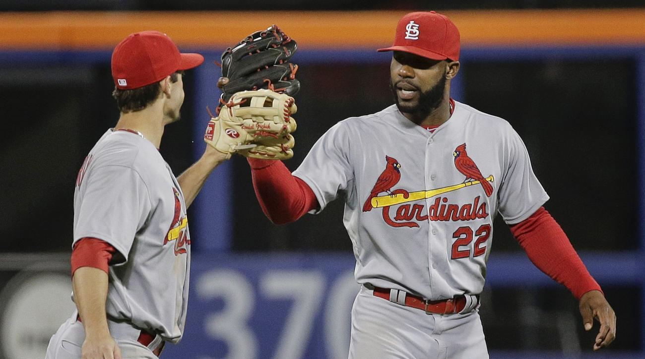 St. Louis Cardinals outfielders Randal Grichuk, left, and Jason Heyward slap gloves after the Cardinals beat the New York Mets 9-0 in a baseball game Wednesday, May 20, 2015, in New York.  (AP Photo/Julie Jacobson)