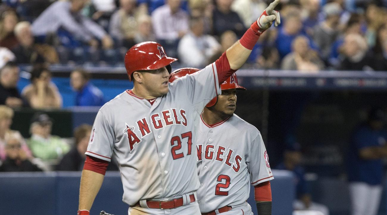 Los Angeles Angels' Mike Trout (27) and Erick Aybar (2) gesture to teammate Marc Krauss after they scored off his two run double during the seventh inning of a baseball game, Wednesday, May 20, 2015 in Toronto. (Chris Young/The Canadian Press via AP) MAND