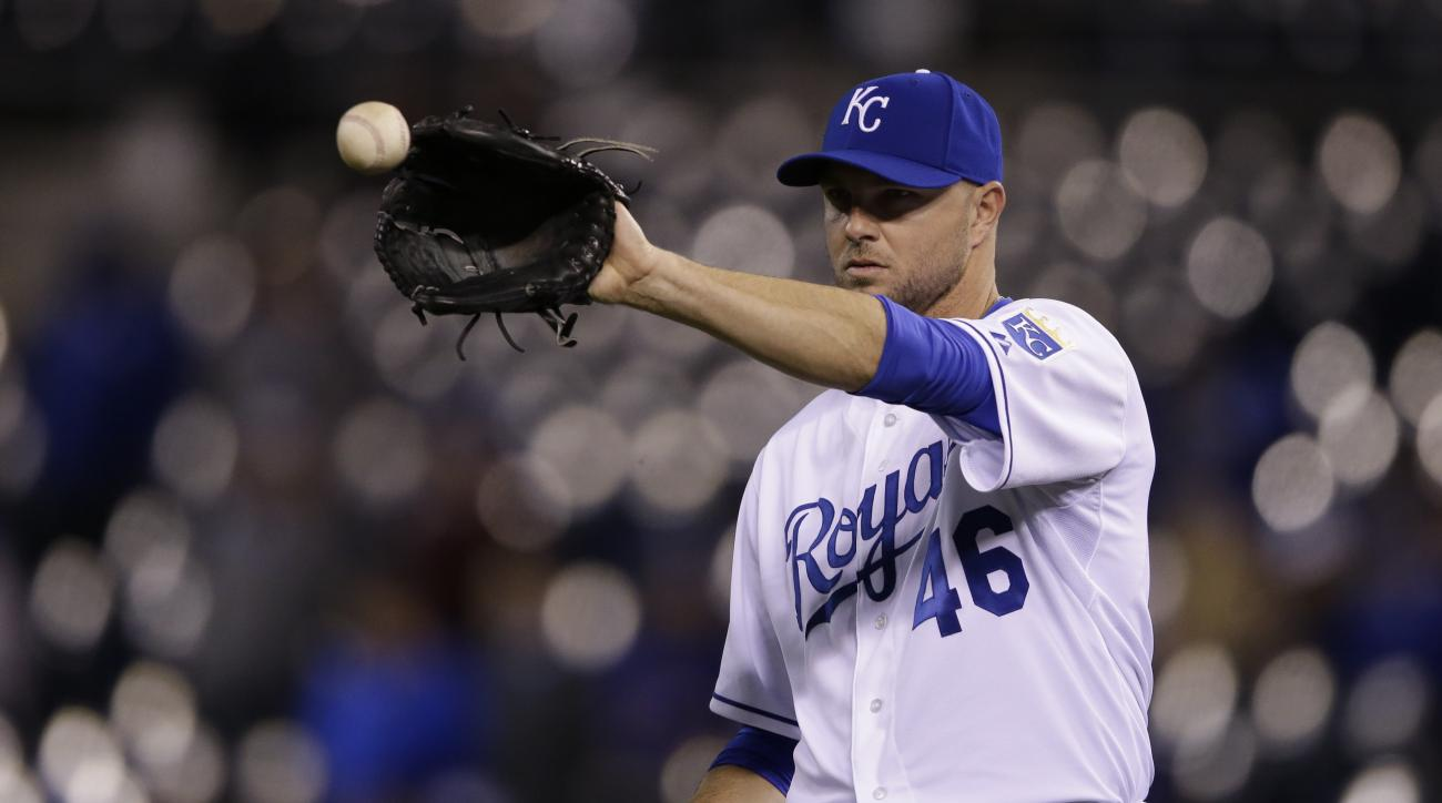 In this Monday, April 20, 2015,  photo, Kansas City Royals relief pitcher Ryan Madson (46) gets a ball following an out during a baseball game against the Minnesota Twins at Kauffman Stadium in Kansas City, Mo. After signing with the American League champ