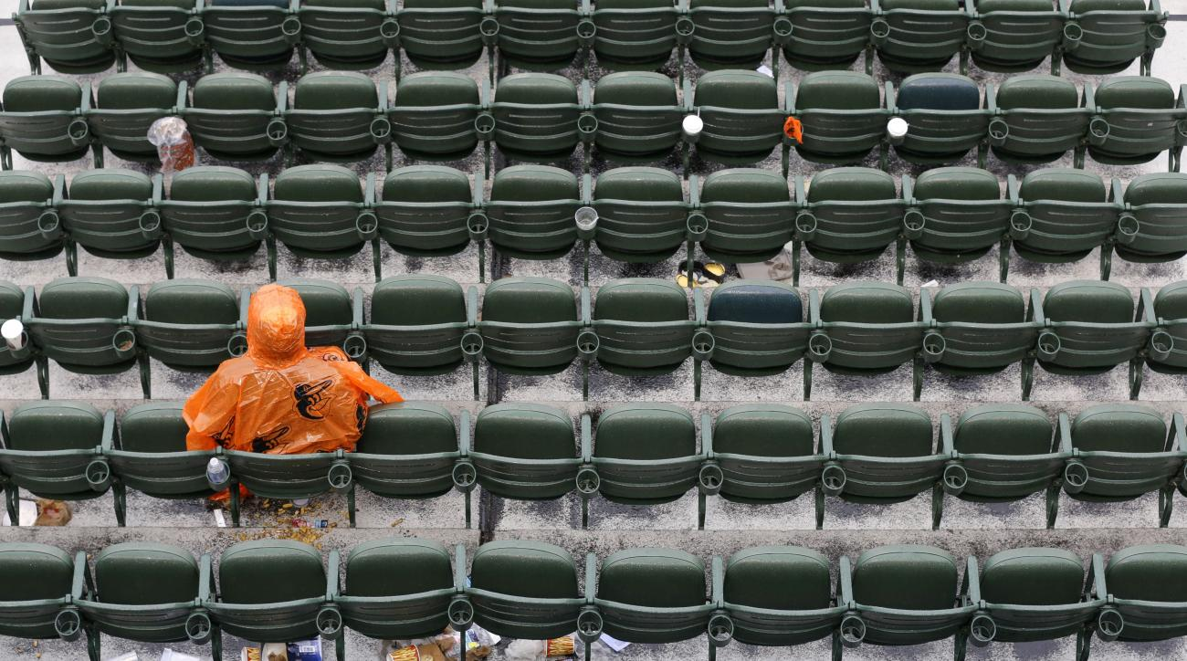 A Baltimore Orioles fan sits alone in the stands during a rain delay at a baseball game between the Orioles and the Seattle Mariners, Thursday, May 21, 2015, in Baltimore. (AP Photo/Patrick Semansky)