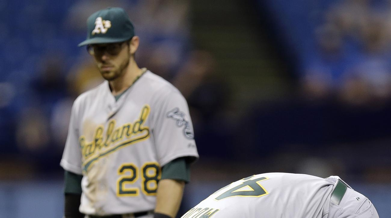 Oakland Athletics relief pitcher Edward Mujica bends over in pain after a ground ball by Tampa Bay Rays' Bobby Wilson cut his thumb during the seventh inning of a baseball game Thursday, May 21, 2015, in St. Petersburg, Fla.  Mujica threw Wilson out at fi