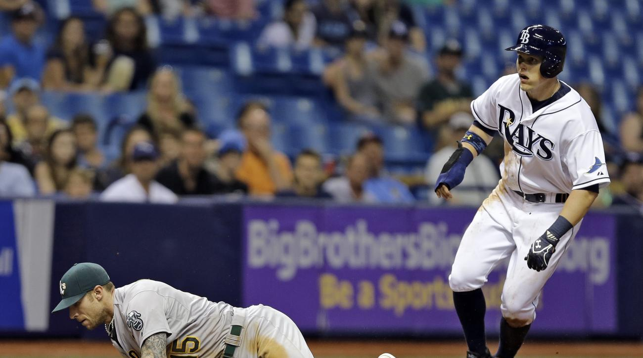 Tampa Bay Rays' Brandon Guyer, right, steals third base as Oakland Athletics third baseman Brett Lawrie fields a wide throw from catcher Stephen Vogt during the seventh inning of a baseball game Thursday, May 21, 2015, in St. Petersburg, Fla.  (AP Photo/C