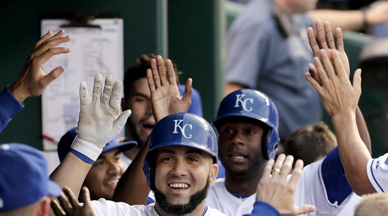 Kansas City Royals' designated hitter Kendrys Morales celebrates in the dugout after hitting a two-run home run during the third inning of a baseball game against the St. Louis Cardinals Friday, May 22, 2015, in Kansas City, Mo. (AP Photo/Charlie Riedel)