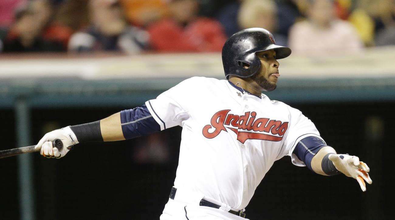 Cleveland Indians' Carlos Santana watches his ball after hitting an RBI-double off Cincinnati Reds relief pitcher Jumbo Diaz in the seventh inning of a baseball game, Friday, May 22, 2015, in Cleveland. Jason Kipnis scored on the play. (AP Photo/Tony Deja