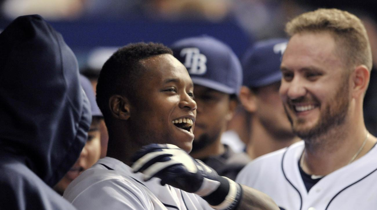 Tampa Bay Rays' Tim Beckham, center, celebrates in the dugout with Kevin Jepsen, right, and other teammates after hitting a solo home run off Oakland Athletics reliever Arnold Leon during the eighth inning of a baseball game Friday, May 22, 2015, in St. P