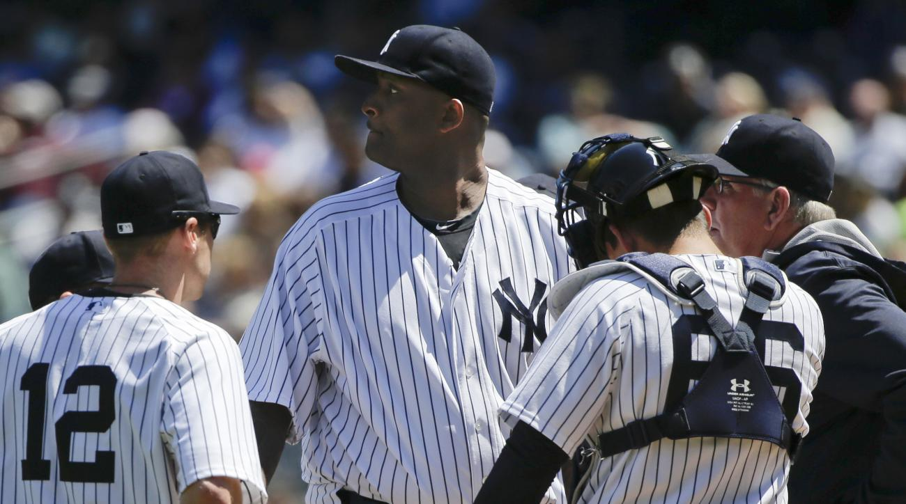 New York Yankees pitcher CC Sabathia, center, talks on the mound with teammates and pitching coach Larry Rothschild during the third inning of a baseball game against the Texas Rangers Saturday, May 23, 2015, in New York. (AP Photo/Julie Jacobson)